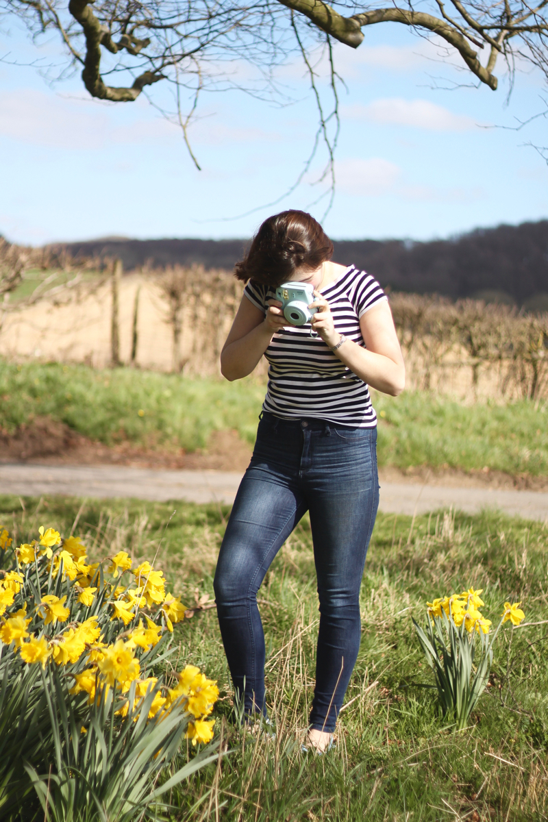 Spring Jeans outfit with daffodils and Polaroid camera