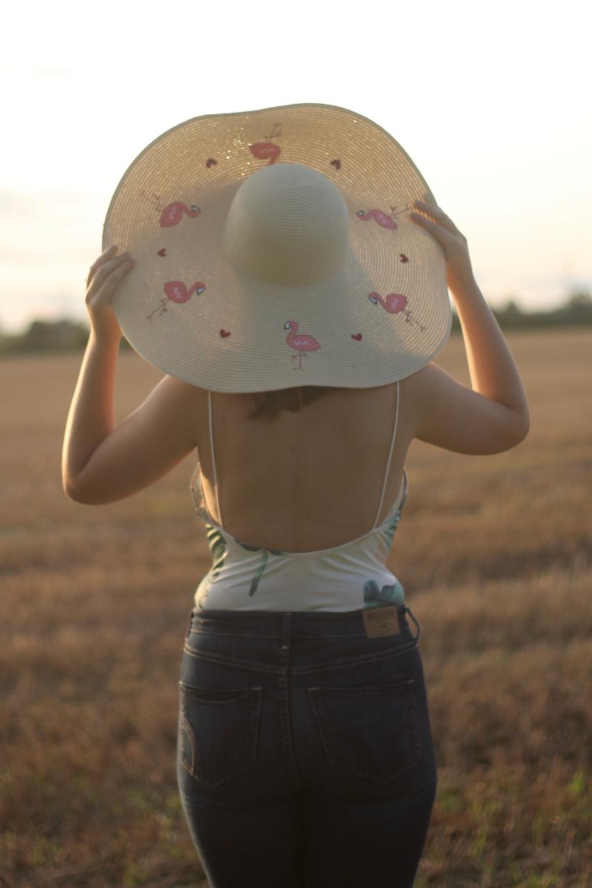 Tobi palm print bodysuit with floppy flamingo hat and jeans