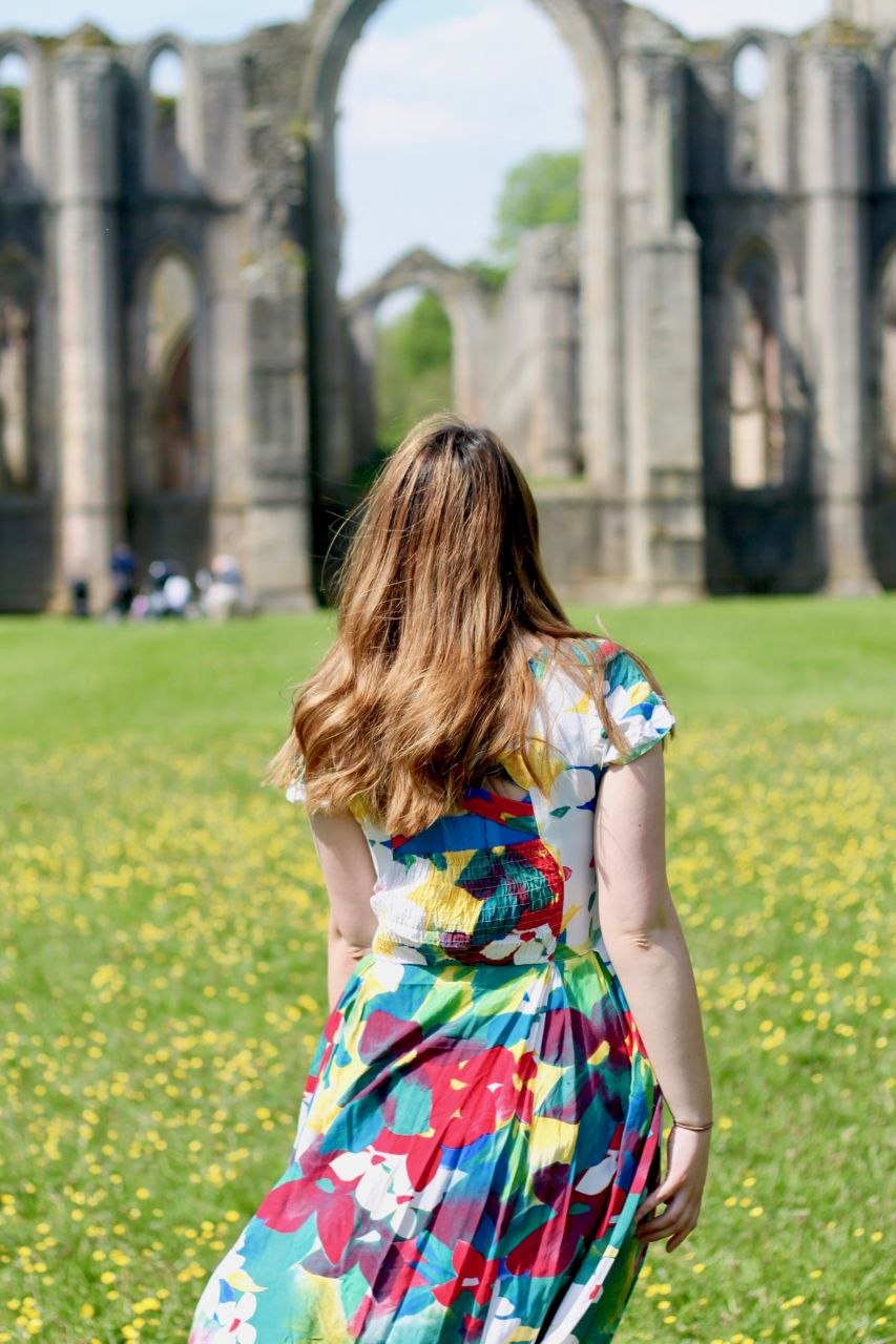 Vintage floral dress in buttercup meadow at Fountains Abbey