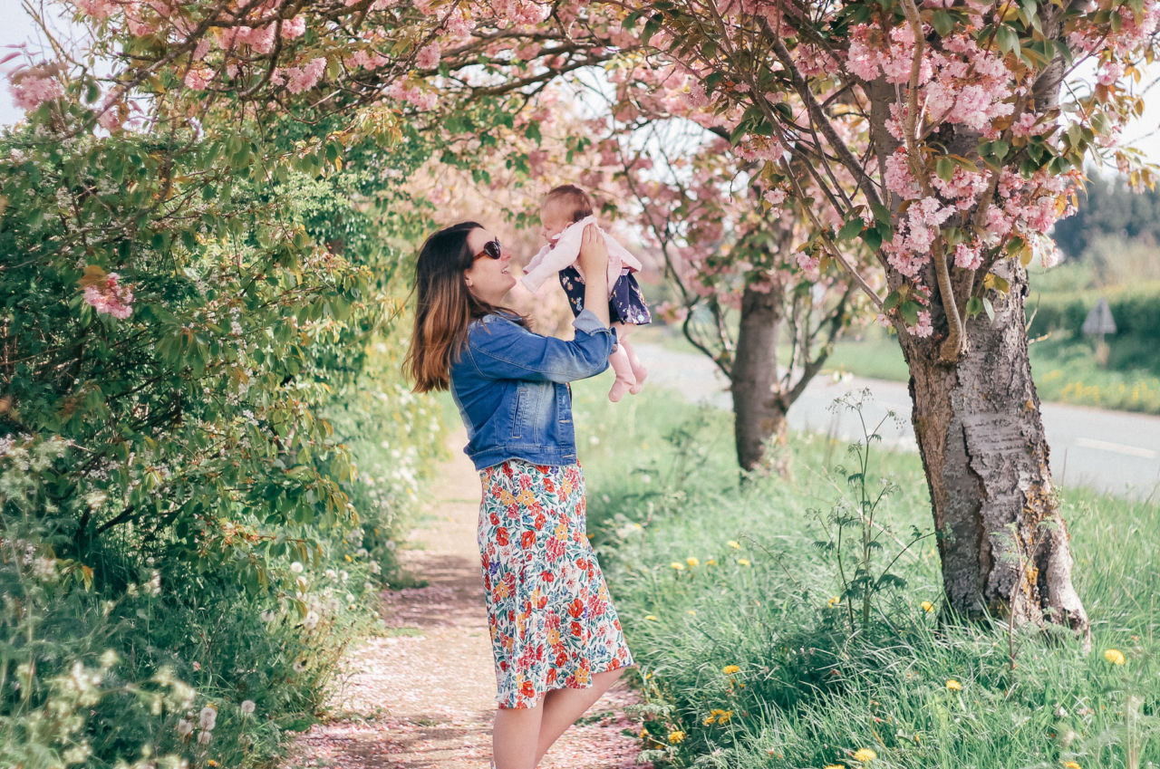 Breastfeeding outfit floral dress among the spring blossoms