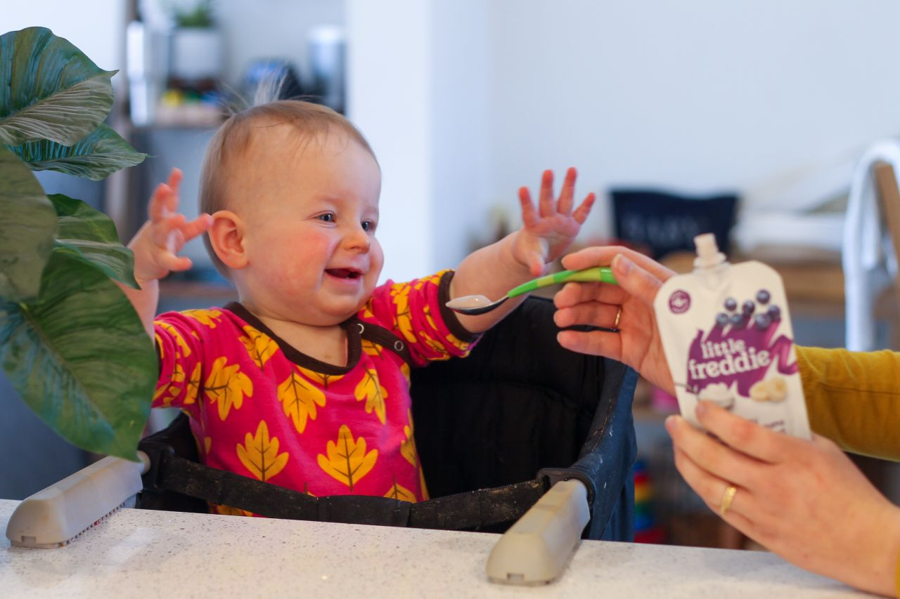 1 year old eating Little Freddie creamy blueberry & banana yoghurt pouch from a spoon