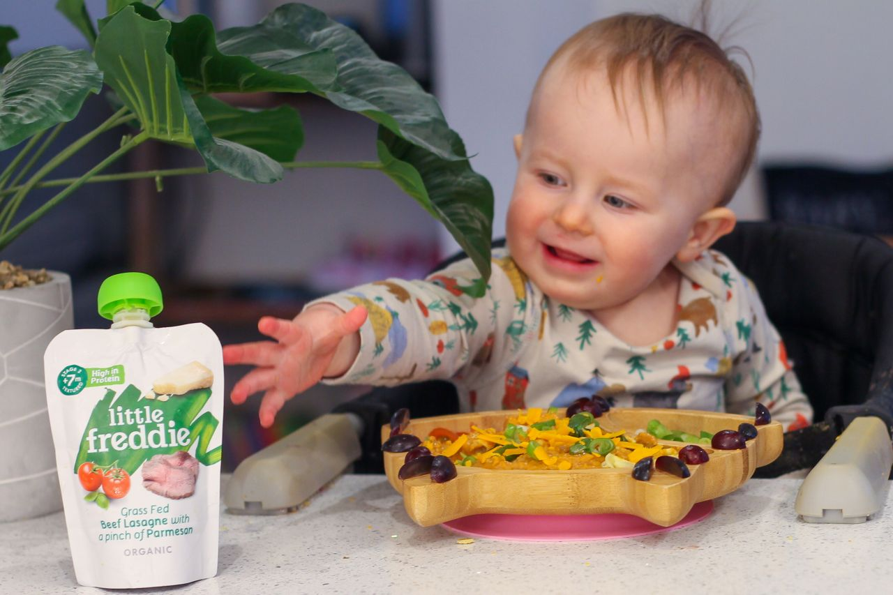 Baby led weaning at 1 year old old - baby reaching for pouch of food